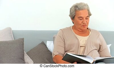 Mature woman looking at her photo album
