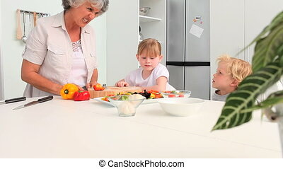 Grandmother cooking with her grandchildren