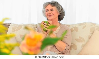 Retired woman drinking her tea
