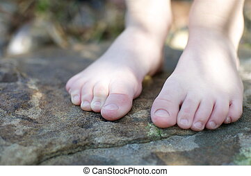 Little Boy with Naked Feet - A little boy stands on a rock...