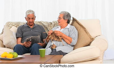 Senior woman knitting while her husband is reading the...