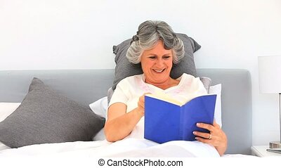 Elderely woman reading a book in her bed