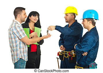 Builder men team give house keys to a couple - Builder men...