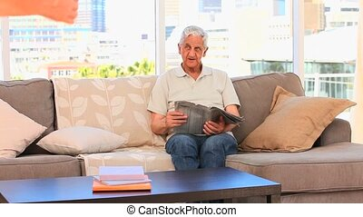 Man reading a newspaper with his wi