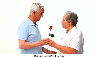 Mature man offering a rose to his w