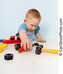 Child playing with a toy plastic constructor