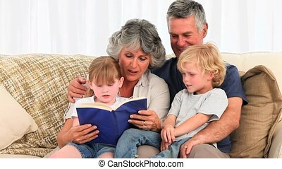 Grandparents reading a book to their grandchildren