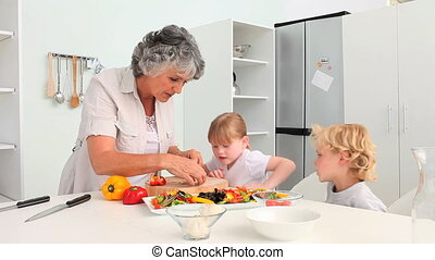Grandmother cooking with her grandc