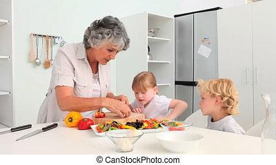 Grandmother cooking with her grandchildren