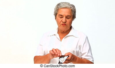 Retired woman eating chocolate - Retired woman eating...