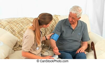 Nurse taking the blood pressure of her male patient