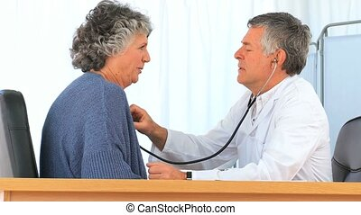 Doctor taking the heartbeat of his mature patient