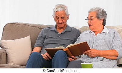 Senior couple looking at their photo album