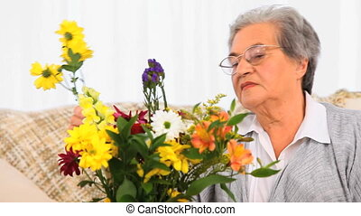 Elderly woman making a brunch of flowers