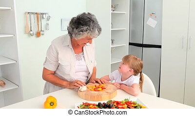 Attentive Grandmother cooking with her granddaughter