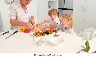 Grandmother cooking with her adorable grandchildren