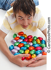 Boy gathering together easter eggs - A boy gathers together...