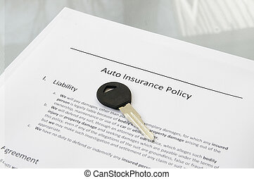 Closeup of a car key and auto insurance policy