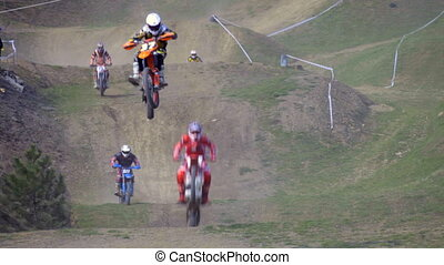 motocross riders race in dry, dusty conditions