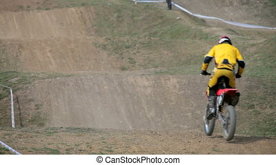Motocross rider race in dry, dusty conditions