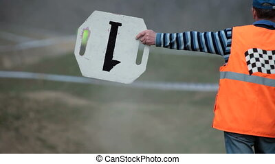 assistant referee for motocross shows the sign