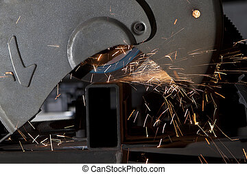 metal cutting saw close up throwing sparks all over in a...