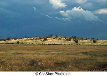landscape - rain building up beyond a hill