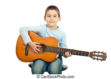 Small boy playing guitar - Small boy sitting on chair and...