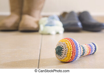 Baby Rattle in front of family shoes