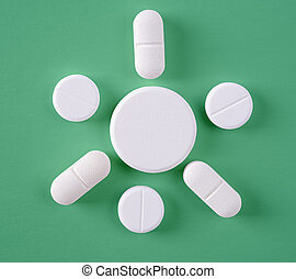 Some of White pills on a green background