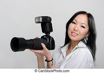 Asian woman with photo camera on white background