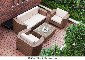 Home exterior patio with wooden decking and rattan sofa view...