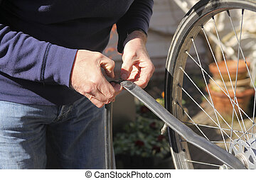 Flat tire repair - Man fixing flat tire of bike