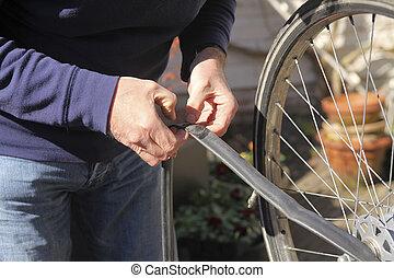Flat tire repair - Man fixing flat tire of bike