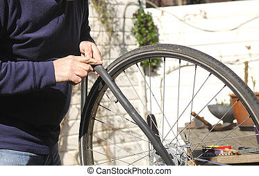 Man repairing bike tire - Man feeling where air escapes from...