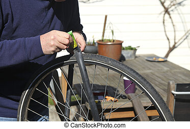 Man repairing bicycle tire - Man putting glue on flat rubber...