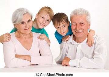 Happy grandparents with their grandsons on a white...