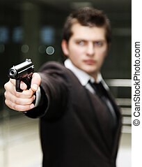 Businessman with gun - A bussiness man with a gun The focus...