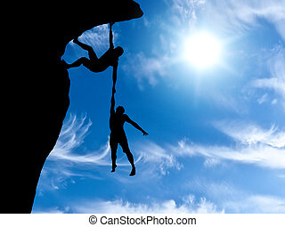 climber clings to a rock plummet with the other hand holding...
