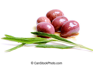 Kalamata olives drizzled in olive oil with olive leaves in...