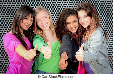 Happy diverse teen girls showing thumbs up