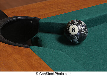 Pool table pocket with the eight ball close by ready for a...