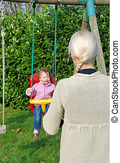 A mother playing with her baby in a swing
