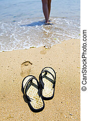 Beach slippers on sand and girl in ocean out of focus