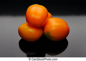 Orange tomatoes on a black backgrouns - Orange and yellow...