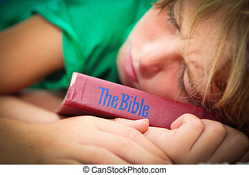 christian child sleeping with well worn and read bible