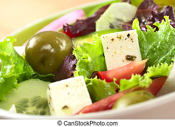Greek salad out of cheese, green olives, tomato, green bell pepper, red onion, cucumber and lettuce (Selective Focus, Focus on the cheese on the right)