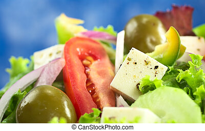 Greek salad out of cheese, green olives, tomato, green bell pepper, red onion, cucumber and lettuce with blue background (Selective Focus, Focus on the cheese)