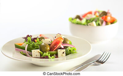 Greek salad out of white cheese, olives, red onions, tomato, bell pepper, cucumber and lettuce with herbs (Selective Focus, Focus on the front of the salad)