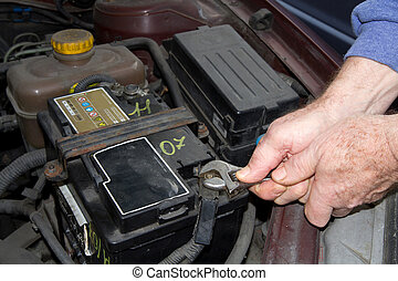 mechanic changing the battery of a car